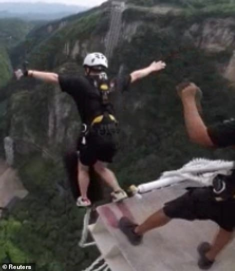 Tourists are helped by an instructor ahead of their bungee jump