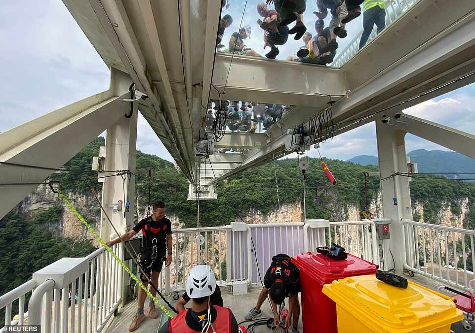 Operators prepare tourists for the 853ft bungee jump from Zhangjiajie Grand Canyon's glass-bottomed suspension bridge