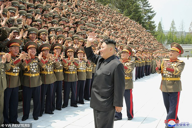 Kim Jong Un waving to a crowd of enthusiastic military officers looking noticeably slimmer in his trademark Mao suit in a photo issued on July 30