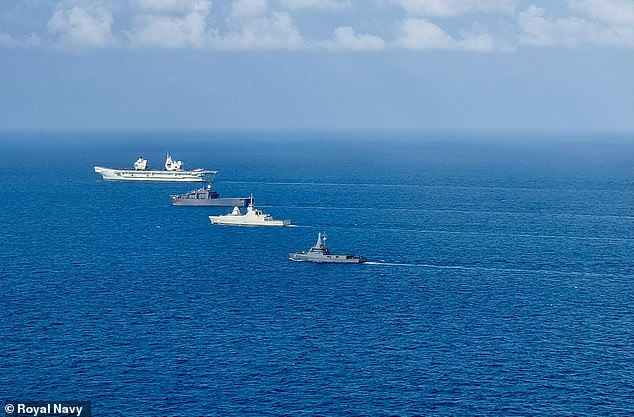 Big Lizzie (far left) has been sailing across the globe accompanied by ships that form the UK strike carrier group, in one of the largest concentrations of British naval power in a generation