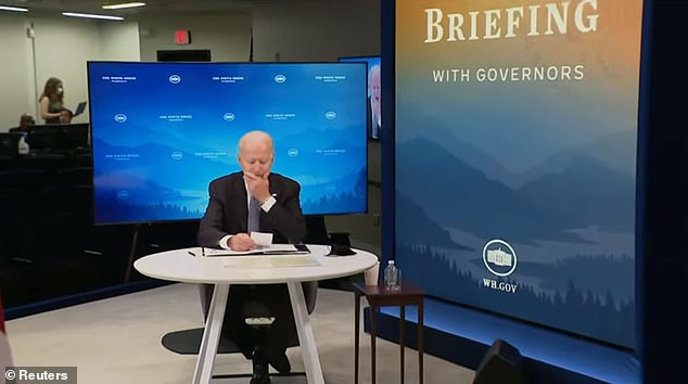After Biden was handed the note, he wiped his chin roughly 20 minutes into the virtual meeting