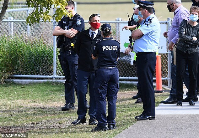 The six new cases are all linked to the Indooroopilly State High School. Pictured is police with the school's acting Principal as the school shuts for deep cleaning
