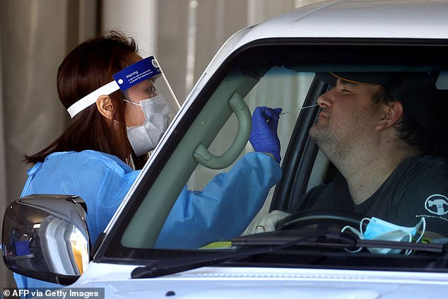 A health worker takes a swab at a drive through testing clinic in Brisbane's east on Saturday (pictured)