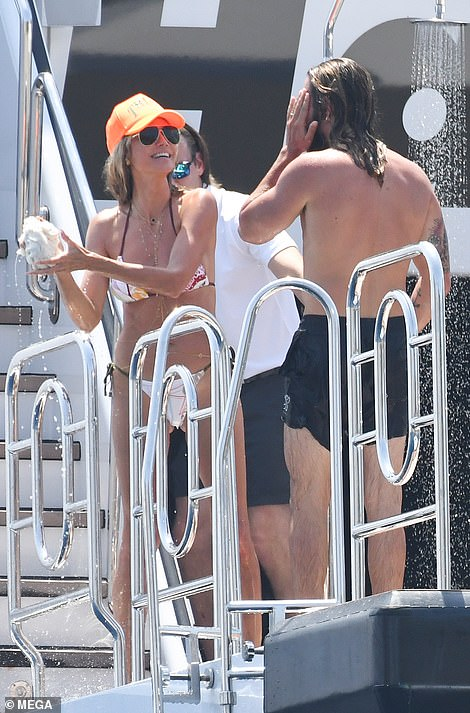Loved-up: Heidi Klum appeared to be in good spirits as she enjoyed another day in paradise and put on a cosy display with her husband Tom Kaulitz, 31, on Saturday