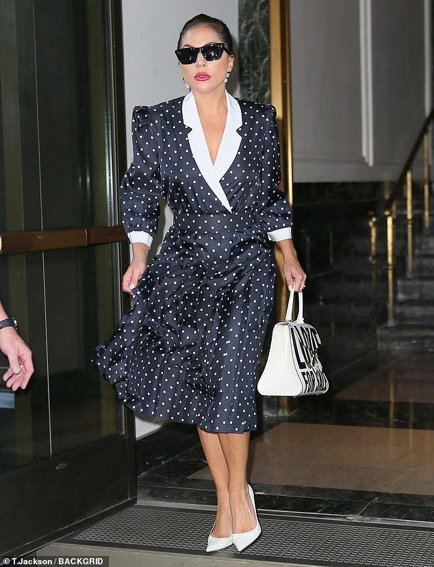 Elegant: Gaga's outfit highlighted her toned legs and featured a plunging white collar with notched lapels and padded shoulders