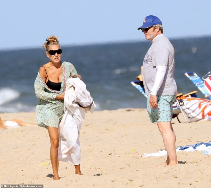 Happy with her family: The longtime star wore a print coverup with her black suit as Matthew was in a T-shirt and shorts with a cap