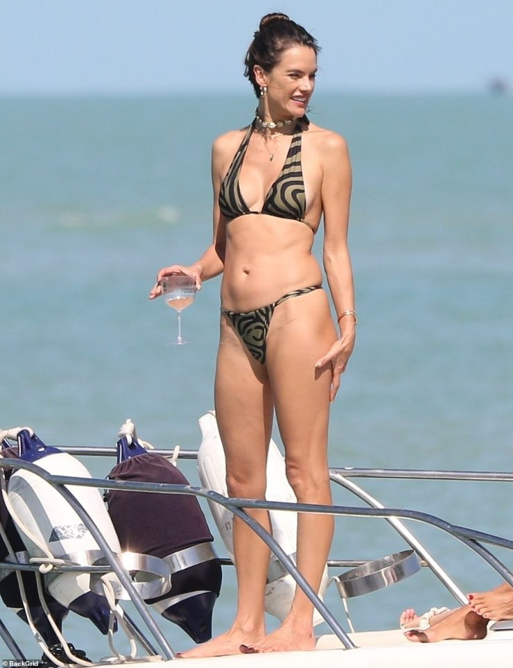 Cheers:On Saturday the leggy wonder - who has worked for Victoria's Secret and now plugs her very own GAL Floripa swimwear line - did her best to show off her toned fame as she paraded down the shore and hopped on a boat