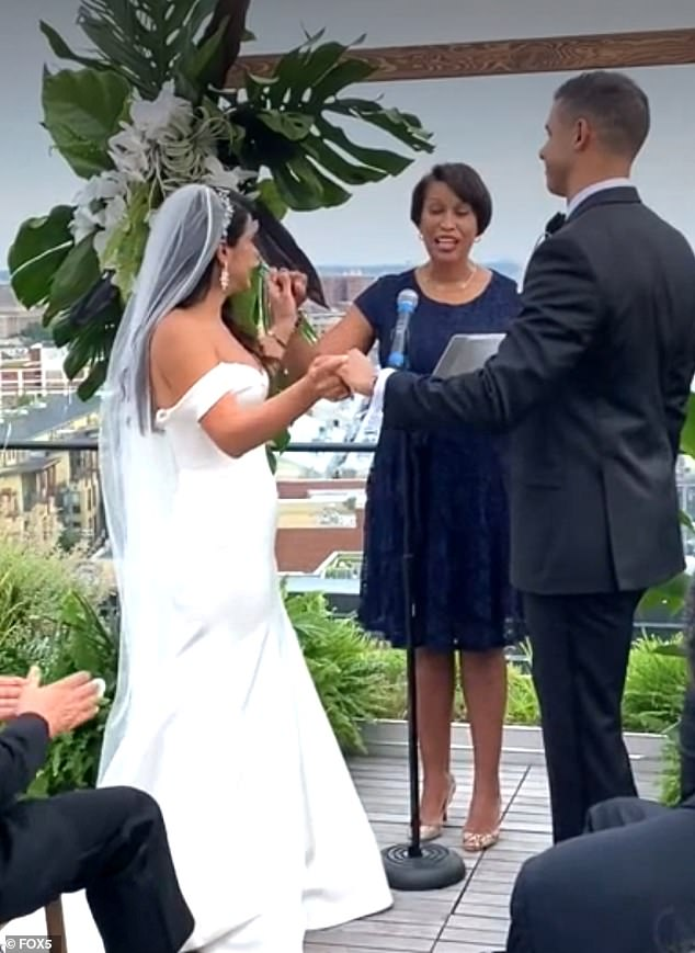 Washington DC Mayor Muriel Bowser was under fire once again this weekend after she was seen officiating a large wedding (pictured), and in another photo from the event she appeared to sit indoors without a mask on, hours after her face covering mandate came back into effect