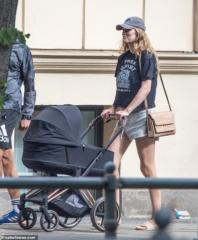 New mother:Toni Garnn stepped out with newborn daughter Luca and husband Alex Pettyfer in Berlin on Saturday - in her first public outing since giving birth last month