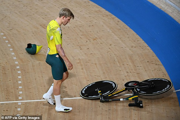 Australia's Alexander Porter looks at his bicycle after crashing during the men's track cycling team pursuit qualifying event during the Tokyo 2020 Olympic Games