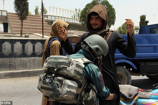 Security officials check people on a roadside checkpoint in Kandahar after thousands were evacuated from their homes