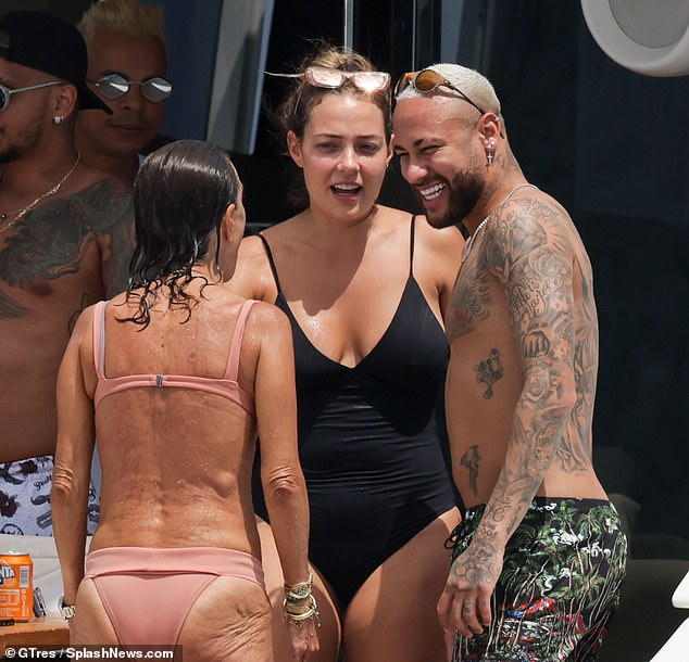 Fun in the sun: Neymar looked elated as he chatted with beauties in swimsuits and sunbathed on a yacht in Ibiza on Monday