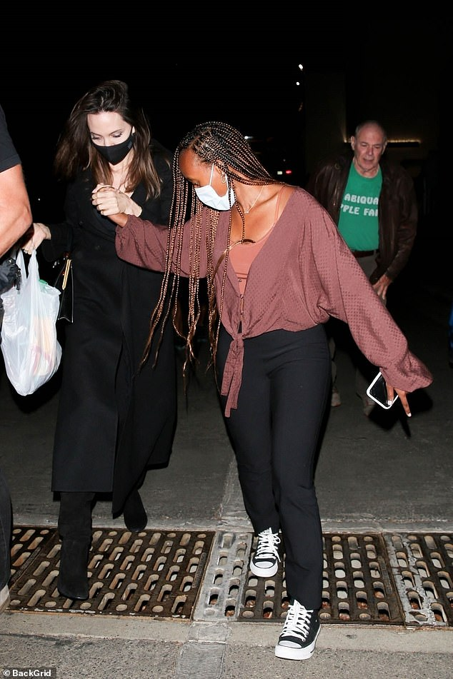 Mind the step!  Angelina cautiously walked through a storm sewer in her suede ankle boots