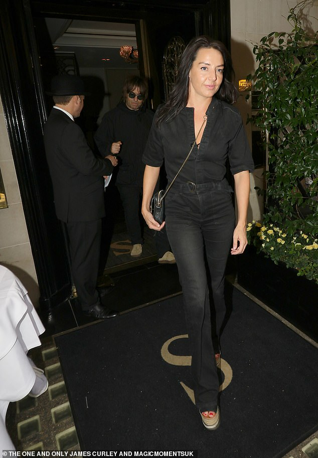 Stylish: Author Debbie opted for a partially unbuttoned black jumpsuit when she stepped out in the capital with her rocking partner
