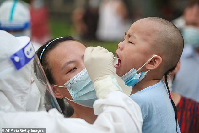 A boy is swabbed for Covid by a medic wearing full PPE at a testing facility inYangzhou in China's eastern Jiangsu province. The city had recorded 126 cases by Tuesday