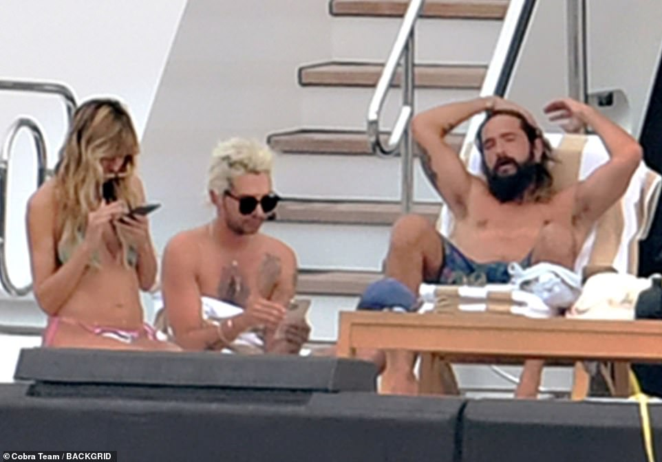 Family matters: The model and her musician husband from Tokio Hotel soaked up the Italian sun by sunbathing with close friends including Tom's brother Bill Kaulitz, 31 (center)