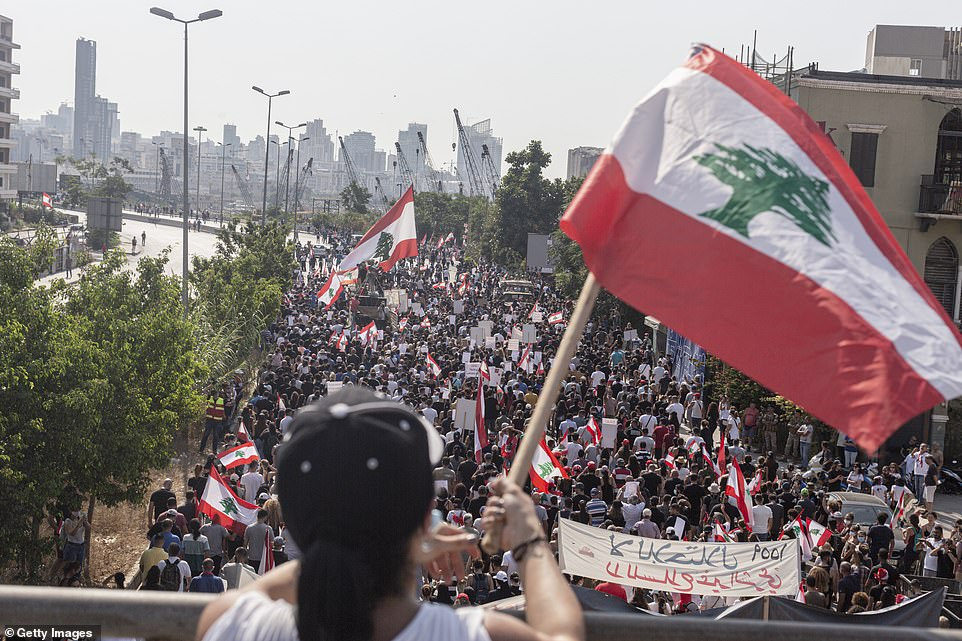 Thousands of demonstrators march past the port in Beirut as they mark one year since the blast