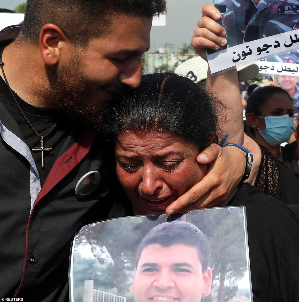 A relative of one of the victims of last year's Beirut port blast weeps while carrying his picture