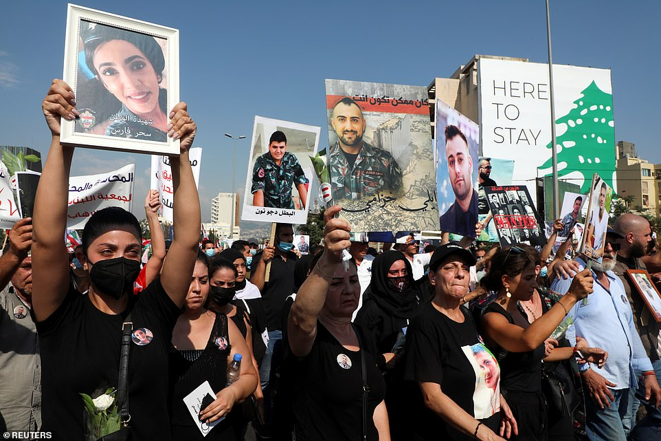 Families of the victims hold up photographs as they mourn their relatives during the protest on Wednesday