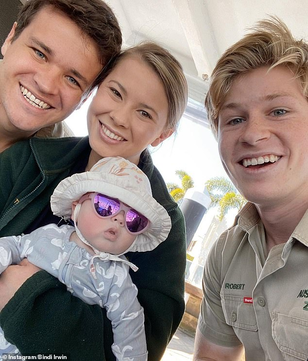 'It's a mood': It's not the first time Bindi has joked about her daughter's sassy side. In early August, she shared this cute picture on Instagram of her baby girl sporting some seriously stylish purple shades and a bucket hat. Pictured with Chandler (left) and Robert Irwin (right)