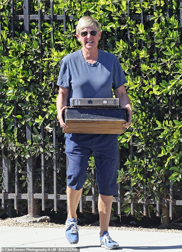 Leaving: DeGeneres carried an old wooden box and a ledger on English sculptor Henry Moore before getting into his limited edition Porsche 911 Targa