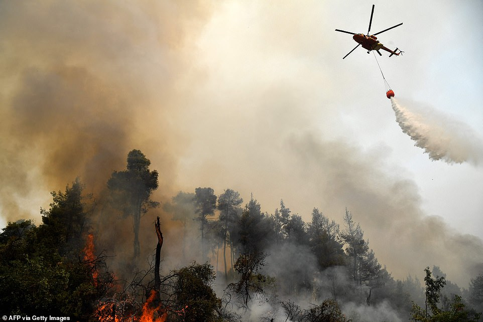 A helicopter pours water on a wildfire on Thursday near the village of Kechries in North Evia