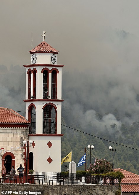 Smoke rises from a hill by the village of Kourkouli, North Evia, on Thursday