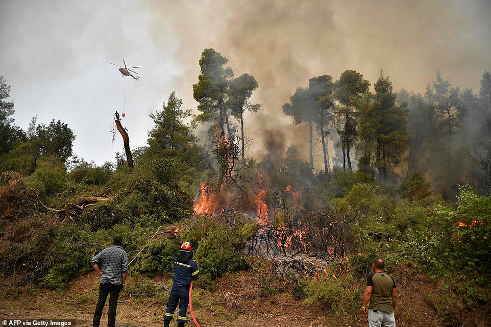 Firefighters douse flames with a hose as they attempt to stop the inferno from reaching the village ofKechries