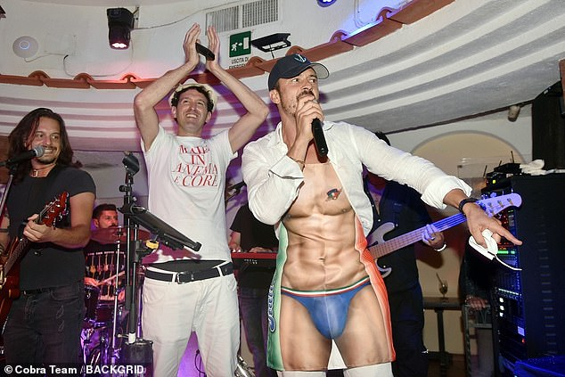 Playful:Orlando threw himself into the celebrations by jumping on a table in a playful apron that mimicked the chiselled physique of an Italian hunk