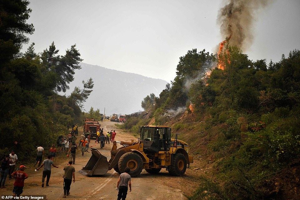 A digger works on a road as fire crews build a controlled fire zone to prevent the blaze to reach the village of Kechries