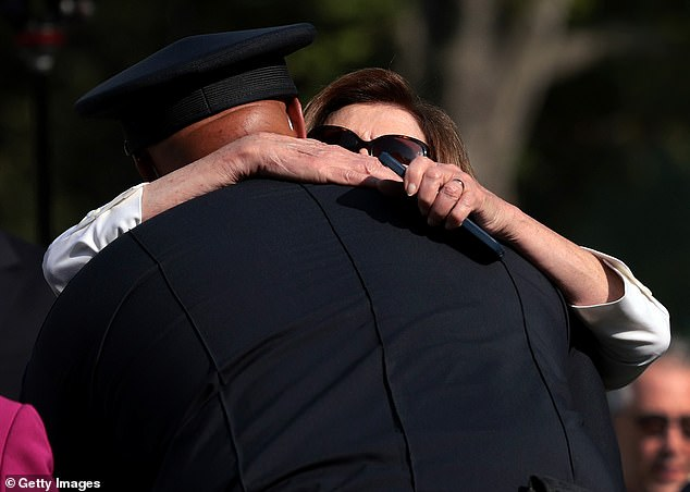 Pelosi hugs U.S. Capitol Police Pfc. Harry Dunn, who last week testified before Congress about the abuse he had suffered as Trump supporters stormed the U.S. Capitol