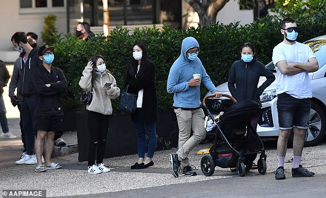 Locked-down Brisbane residents wait in a long queue outside Lune Croissanterie store in South Brisbane. Police patrolled the street to ensure customers were wearing masks and social distancing at its Thursday opening