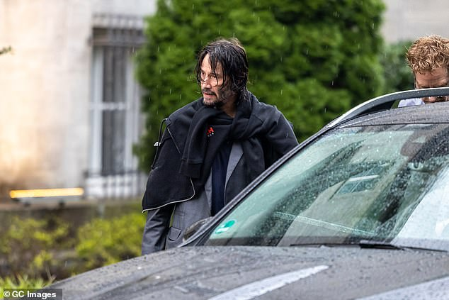 Heading out:Keanu kept one of his hooded jackets wrapped around his shoulders as he headed to his car after leaving the hotel