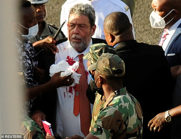 Prime Minister Ralph Gonsalves, 74, was passing through the crowd outside parliament in Kingstown when he got hit by a projectile. Above, Gonsalves is covered in blood following the attack