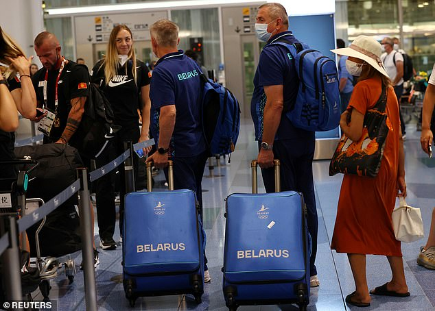 The coaches collect their bags as they board a flight back to Minsk from Tokyo on Friday