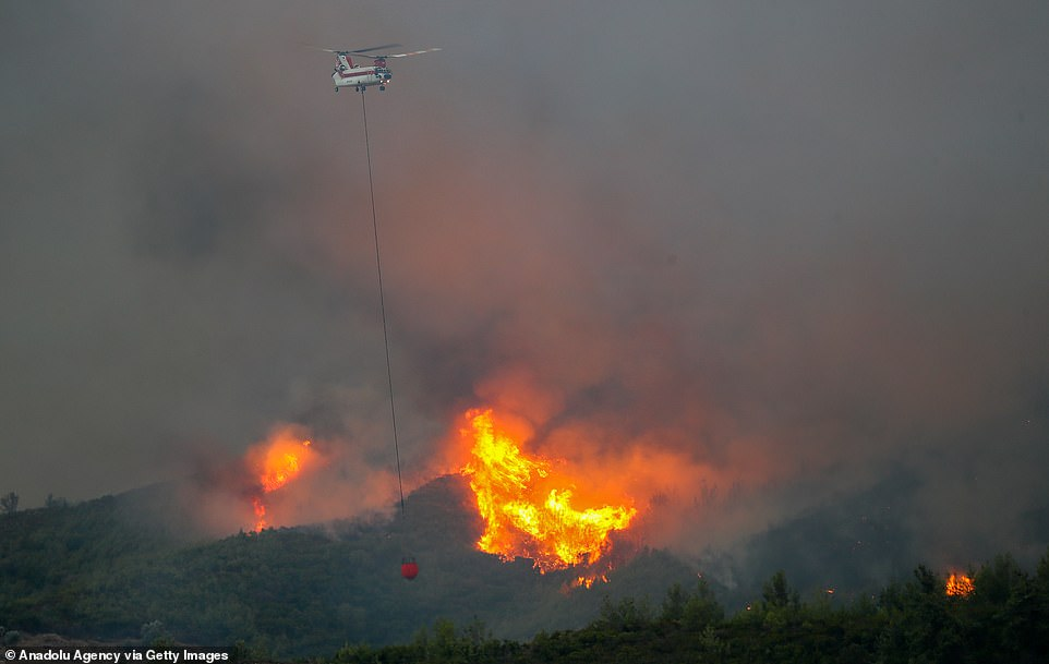 A helicopter dumps water onto the burning forests in Mugla, Turkey on August 5.In coastal Mugla province, where the tourist destinations of Bodrum and Marmaris are located, fires continued to burn in three areas on Friday, officials said