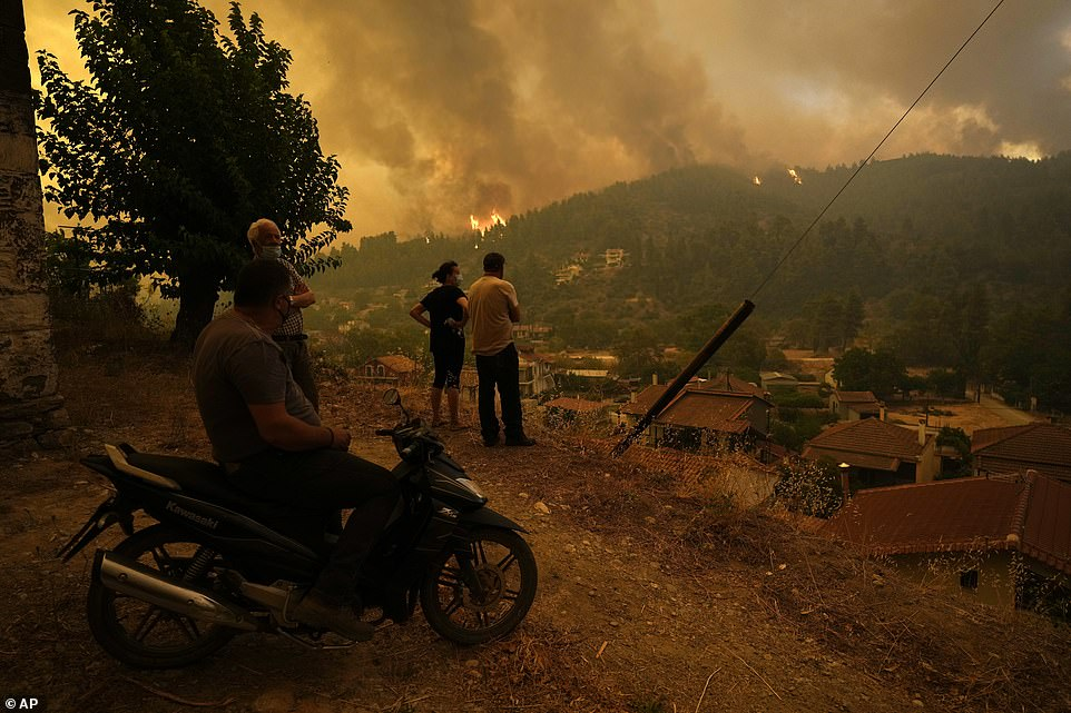Local residents stand on a hill as flames approaching at Gouves village on the island of Evia
