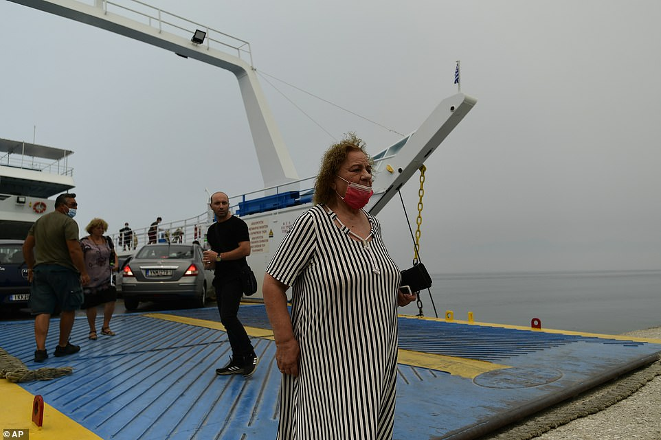 A ferry arrives with evacuees from the burning Evia island at Arkitsa port in mainland Greece