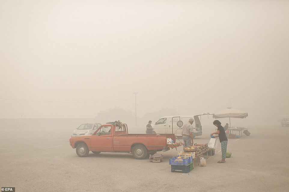 Heavy smoke from the fires blanketed a market on the island of Evia today (pictured) while also blocking out the sun, turning the sky an eerie orange colour