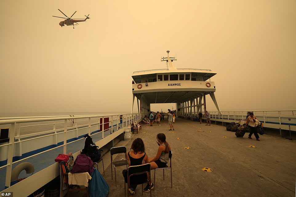 Hundreds of locals have been evacuated by boat while water-carrying helicopters circle overhead, trying to douse the flames