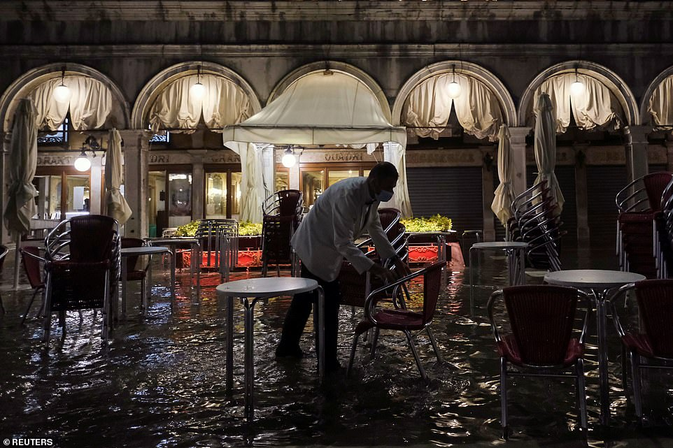 A restaurant worker clears away tables and chairs in the ankle-deep water last night
