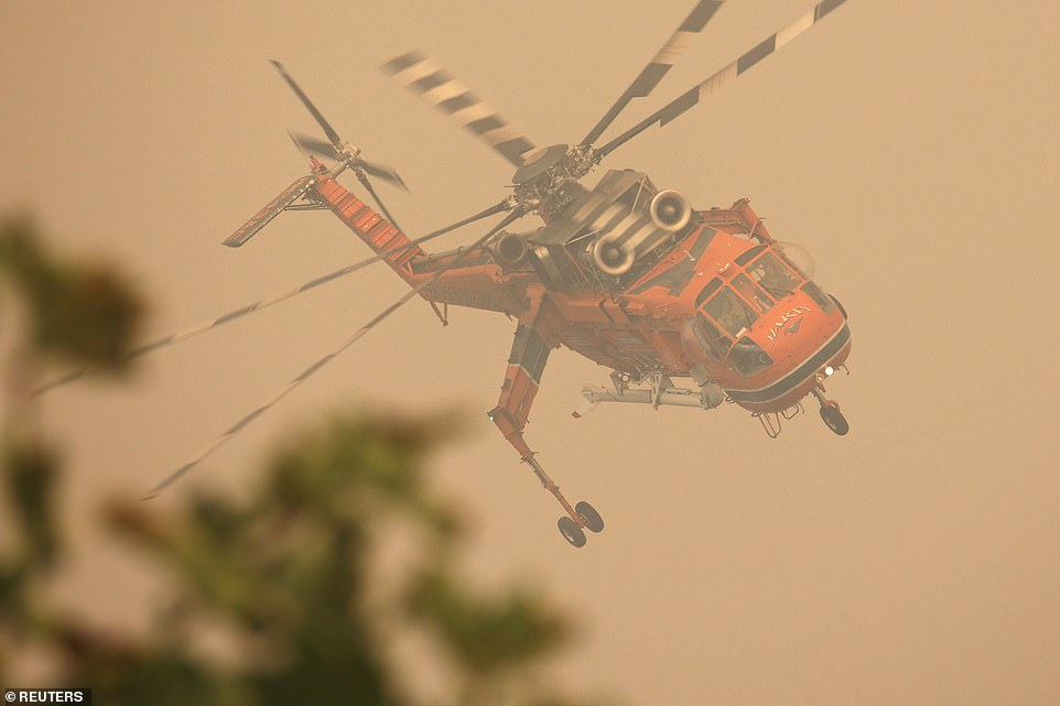 A firefighting helicopter flies over a wildfire burning in the village of Galatsona, on the island of Evia