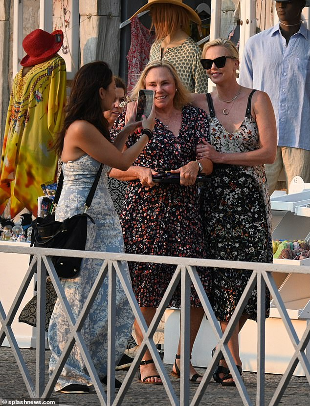 All about the accessories: Charlize teamed her dress with a pair of black sandals and donned wayfarer shades, injecting some glitz with a moon shaped pendant