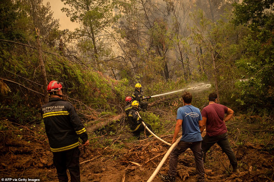 Serbian firefighters and volunteers use a water hose to extinguish the Evia fire, one of around a dozen currently burning in Greece, but by far the most widespread and severe