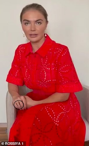 Looking tanned in a red dress,Alina Kabaeva, 38, wore what appeared to be a wedding ring on her right hand in view of the camera.