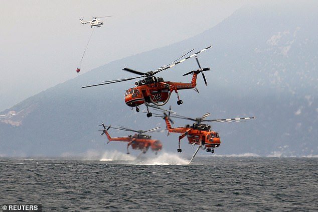 Firefighter helicopters are filled with water off the beach of the village of Pefki as emergency services continue to tackle wildfires in Greece