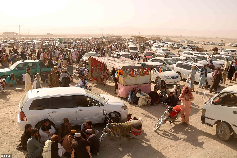 Men wait with their cars at the Spin Boldak border crossing with Pakistan, amid reports that it will reopen on Thursday