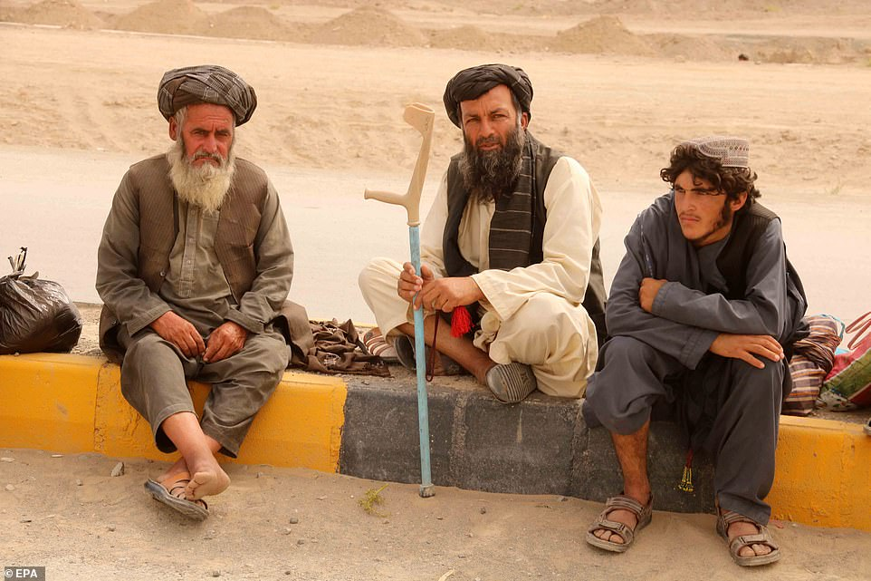 Afghani men wait near the border crossing between Pakistan and Afghanistan for the gates to reopen