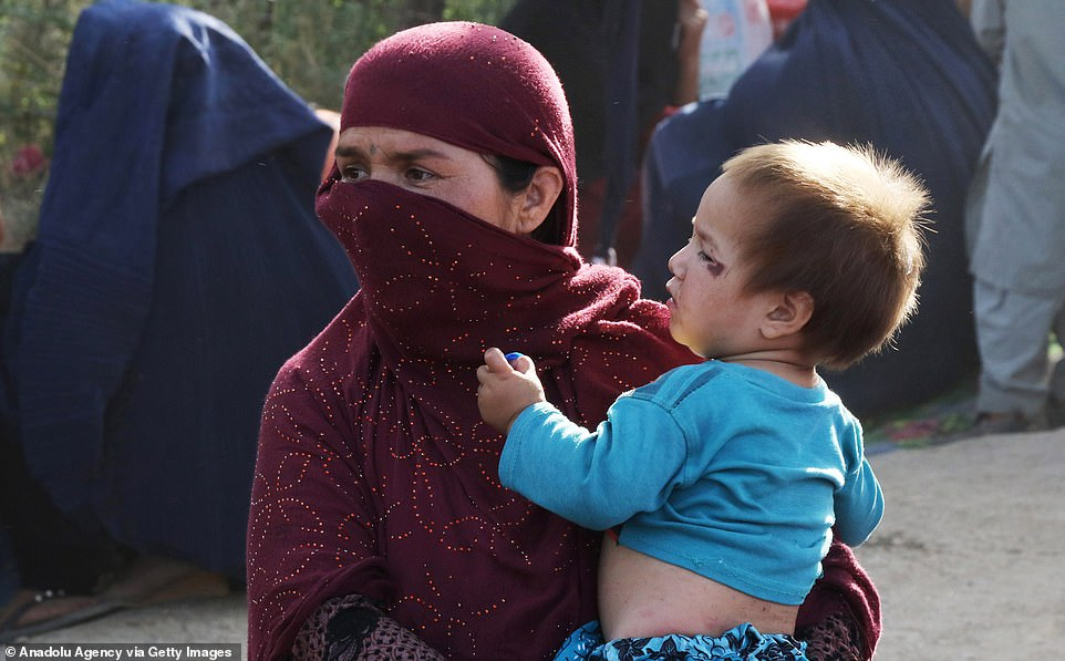 A woman carries her child through a refugee camp in the Afghan capital of Kabul where thousands are now living after being displaced by fighting elsewhere in the country