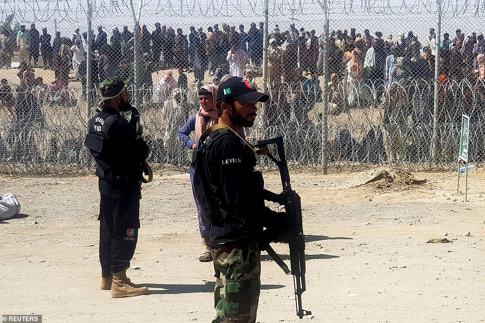 Pakistan's paramilitary soldiers stand guard in front of people who gather and wait to cross at the Friendship Gate crossing point in the Pakistan-Afghanistan border town of Chaman. Pakistan, which has seen the largest number of Afghan refugees cross its border, has refused to take any more